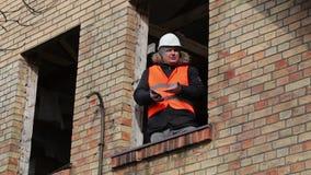 Administrador del sitio enojado con la tableta en la ventana de la segunda planta del edificio almacen de metraje de vídeo