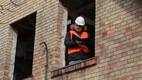 Administrador del sitio que comprueba la documentación en la ventana de la segunda planta del edificio almacen de metraje de vídeo