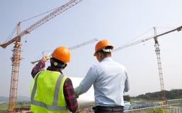 Administrador del sitio y trabajador de construcción que comprueba planes Imagen de archivo libre de regalías