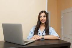 Administrador hermoso de la mujer joven en la recepción que trabaja en el ordenador portátil imagenes de archivo