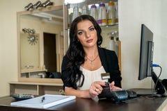 Administrador no salão de beleza que faz o pagamento com terminal fotos de stock royalty free