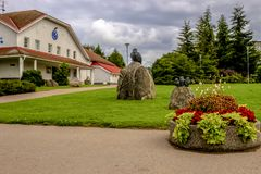 Administrative building in Maardu, Estonia. A modern building with a clock on the facade. Grassy lawn, flower beds, pine trees and shrubs, walkways, sculpture Royalty Free Stock Images