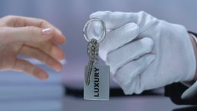 Administrator hand giving luxury room key to female vip client, hotel services. Stock footage stock video