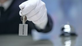 Administrator holding keys to Reserved room, luxury hotel, hospitality services. Stock footage stock footage