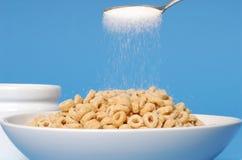 Administrez arroser à la cuillère le sucre sur un bol de céréale d'avoine sur le backgroun bleu Image stock