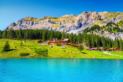Admirable alpine lake with forest and high mountains, Oeschinensee, Switzerland. Famous travel and touristic place, beautiful alpine lake and high mountains with royalty free stock image