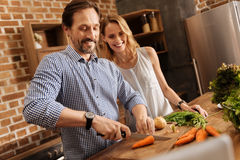 Admirable gallant man cooking for his lady. Real gentleman. Witty wonderful positive guy showing off his skills while chopping carrots and making a dinner for Stock Photography