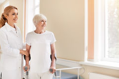 Admirable motivated lady learning walking again. Still using crutches. Bright energetic elderly women going through a rehabilitation while recovering from the Royalty Free Stock Image