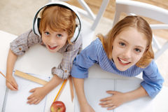 Admirable positive siblings having fun while doing home assignment stock photos