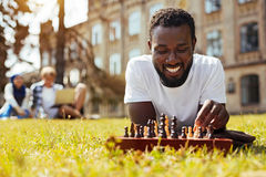 Admirable young man training his cognitive skills. Brainy entertainment. Committed lively smart guy using chess for developing his thinking abilities and Stock Photography