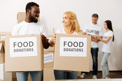 Admirable young people happy volunteering. Positive atmosphere. Charming friendly sincere men and women working in charity foundation and carrying boxes with Royalty Free Stock Images