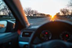 Admiración de la puesta del sol a través de la ventanilla del coche imagenes de archivo