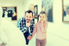 Admiración del padre y de la hija con respecto a pinturas en museo Imagenes de archivo