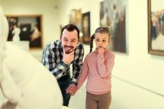 Admiración del padre y de la hija con respecto a pinturas en museo Foto de archivo libre de regalías