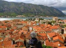 Admirando a cor alaranjada telhou o telhado da cidade de Kotor e da baía velhas de Kotor da fortificação de Kotor, Montenegro Imagem de Stock Royalty Free