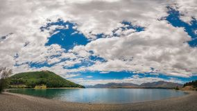Admire the beautiful Panorama of Lake Tekapo, New Zealand. Panorama of the beautiful lake Tekapo in New Zealand with the Southern Alps mountain range in the Royalty Free Stock Image