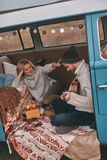 Admired by him. Top view of handsome young men playing guitar for his beautiful girlfriend while sitting in blue retro style mini van stock images