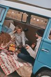 Admired by his talent. Top view of handsome young men playing guitar for his beautiful girlfriend while sitting in blue retro style mini van stock images