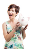 Admired woman with a piggy bank. Isolated over a white background royalty free stock images
