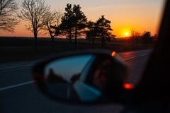 Admirer le coucher du soleil par la fen?tre de voiture images stock