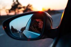 Admirer le coucher du soleil par la fen?tre de voiture photographie stock libre de droits