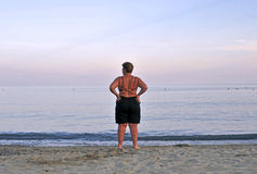 Admiring. Woman on the shoreline contemplating the horizon at the sunset Stock Photography