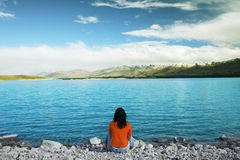 Admiring beautiful New Zealand Lake. Asian woman sitting in front of a Lake, enjoying beautiful view of New Zealand mountains Stock Photo