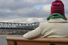 Admiring the bridge. Picture of a girl waiting on the bench admiring the scenery on a cold day Royalty Free Stock Images