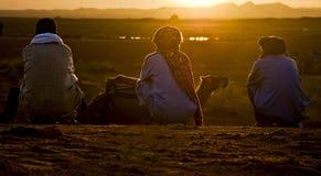 Admiring the dawn. Three Berbers admiring the dawn in the desert (Erg Chebbi, Morocco Royalty Free Stock Photos