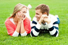 Admiring love couple lost in each other. Happy smiling couple relaxing on green grass. Outdoor shot Royalty Free Stock Photo