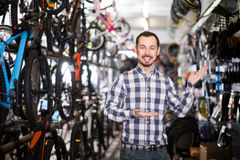 Admiring man in bicycle shop chooses for himself sports bike Royalty Free Stock Photo