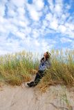 Admiring the sky. Girl sitting on a sand dunes and admiring the beauty of sky Stock Images
