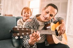 Smiling fascinated boy observing his father`s masterful guitar playing. royalty free stock photography
