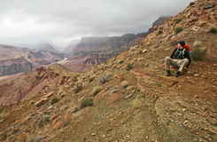 Admiring the view. A hiker rests to admire the expansive view of the Grand Canyon Stock Image