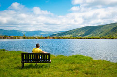 Admiring the view. A male teenager sitting on a bench, admiring the view of the lake Stock Photos