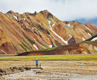 The  admiring woman -turist. Pink and orange Mountains National Park Landmannalaugar in Iceland. Snow remained on the mountains last year. At the foot of the Royalty Free Stock Photos
