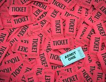 Admit One Amongst Red Tickets. Admit One ticket on top of pile of red tickets royalty free stock photo