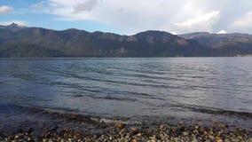 Admita el lago Traful, chalet Traful Ondas en agua cristalina con las montañas en el fondo almacen de video