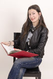Ładna azjatykcia dziewczyna w czarnej kurtce z czerwoną książką. Zdjęcie Stock