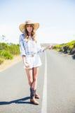 Ładna blondynka hitchhiking na drodze Obraz Stock