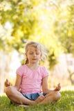 Ładna blondynki dziewczyna medytuje przy parkiem Zdjęcia Royalty Free