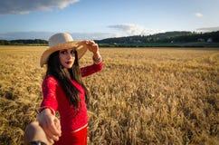 Ładna brunetka bierze ja w pszenicznym polu Zdjęcie Royalty Free
