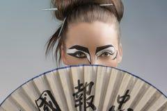 Ładna brunetka w Japan stylu z fan na twarzy Fotografia Royalty Free
