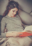 Ładna dziewczyna czyta książkę przy kanapą Obraz Stock
