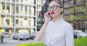Ładna dziewczyna opowiada telefon na ulicie zbiory wideo