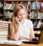 Ładna dziewczyna pisać na maszynie na laptopie i opowiada na telefonie w bibliotece Fotografia Royalty Free
