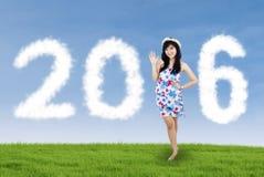 Ładna dziewczyna tworzy liczby 2016 przy polem Zdjęcie Royalty Free