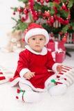 Ładna dziewczynka w Santa kostiumu obsiadaniu Zdjęcia Royalty Free