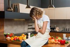 Ładna gospodyni domowa w kuchennym obsiadaniu na stole Fotografia Royalty Free