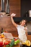 Ładna gospodyni domowa z telefonem komórkowym w kuchni Zdjęcie Royalty Free